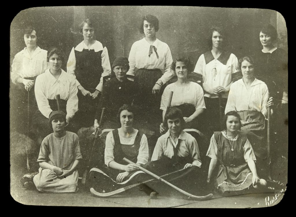 Image is of a women's hockey team circa 1909. The women stand, sit on chairs and sit on the ground in three rows. The hold hockey sticks.  Siren Sport. Women's sport.