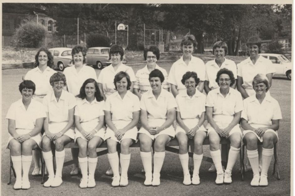 Image is a black and white photo of the Australian women's cricket team who played in the 1973 world cup. The women are lined up in two rows, the back row standing and the front row sitting. They wear white shirts, white skirts with white shoes and white socks pulled up to their knees.