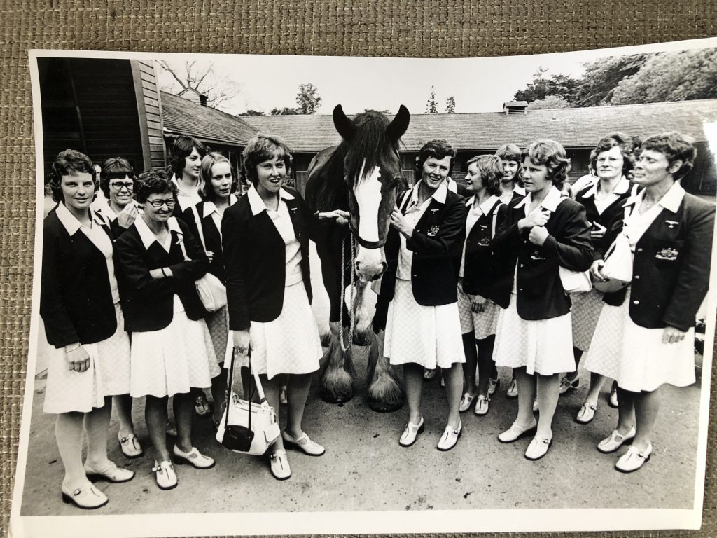 Image os the 1976 Australian women's cricket team in England. They wear their official uniform, including a white skirt and shirt with a dark jacket and they pose with a clydesdale. Siren Sport. Anne Gordon.