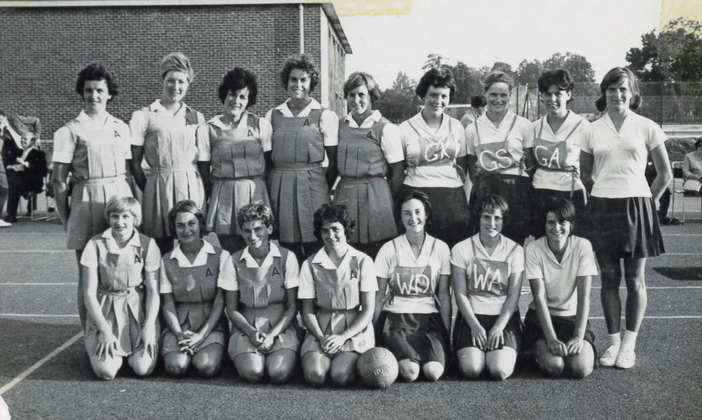 Image is a black and white photo of the Australian netball team at the 1963 World Cup. There are sixteen women in the photo. Nine stand and seven kneel in front of them. They were shirts and skirts and netball tunics.