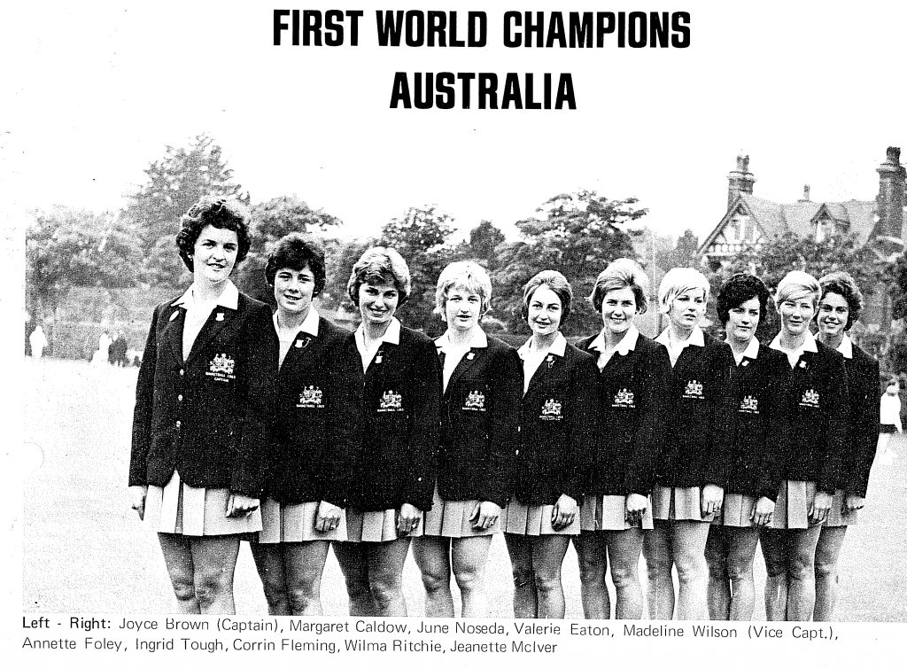 Photo is of the 1963 Netball World Cup winning Australian team. Ten women stand in a line, they wear netball skirts and dark blazers with the Australian coat of arms. Siren Sport.