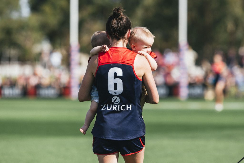 Daisy Pearce carries her infant twins post-game. Image: She Scores