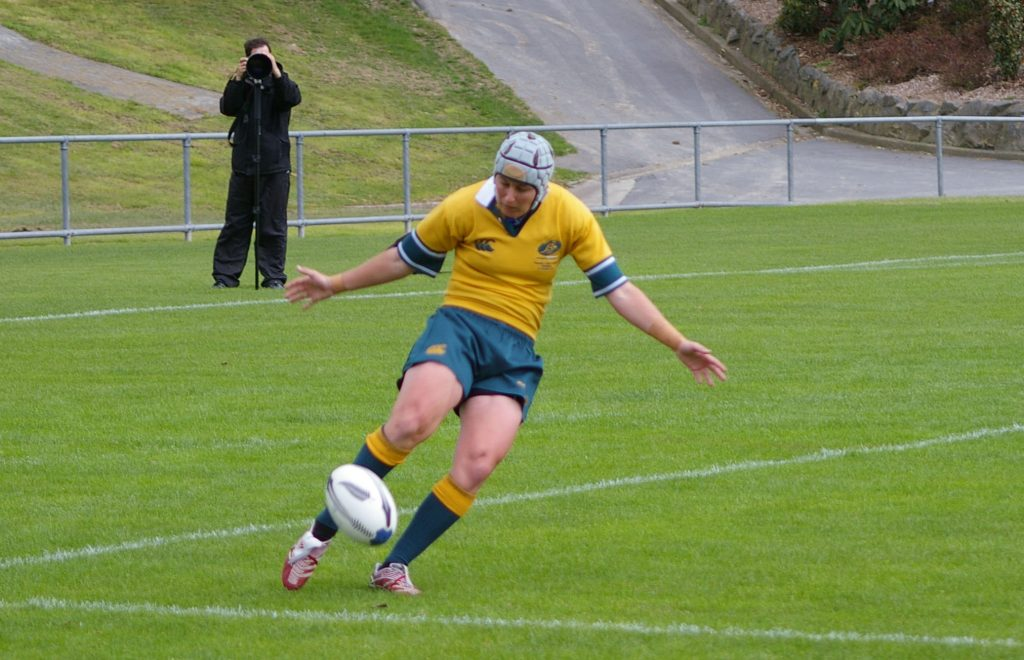 Image is of Alana Thomas playing rugby. She wears the green and gold Australian Wallaroos uniforms. Her arms are stretched out and she looks down towards the ball she is about to kick.