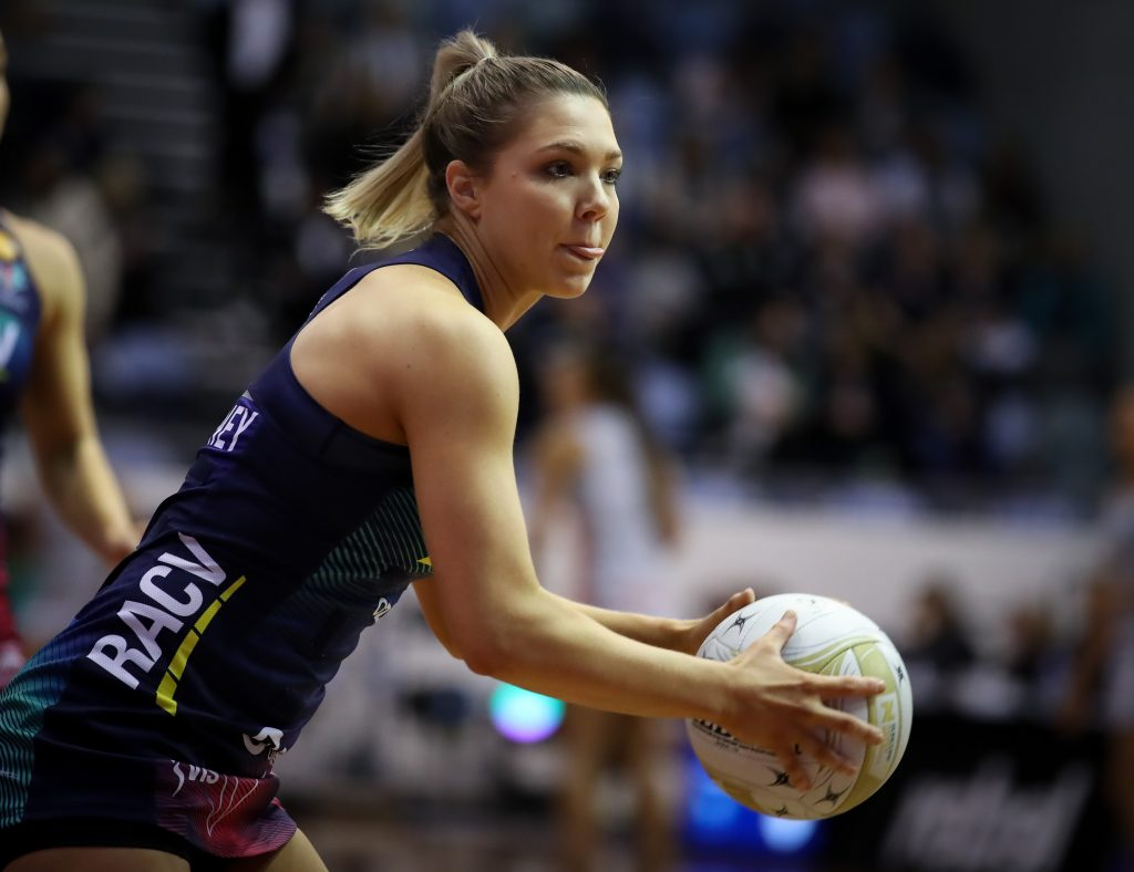 Image is of Melbourne Vixens captain Kate Moloney playing netball. She holds the ball with both hands, and leans forward slightly as she prepares to pass to a teammate.