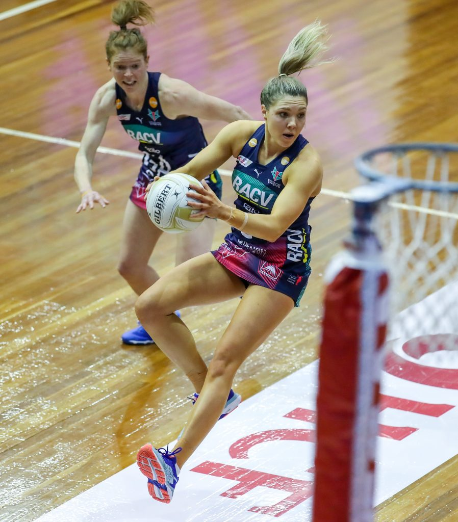 Image is of Melbourne Vixens captain, Kate Moloney in action on the court. She is mid jump after catching the ball. Behind her, a teammate is ready to assist.