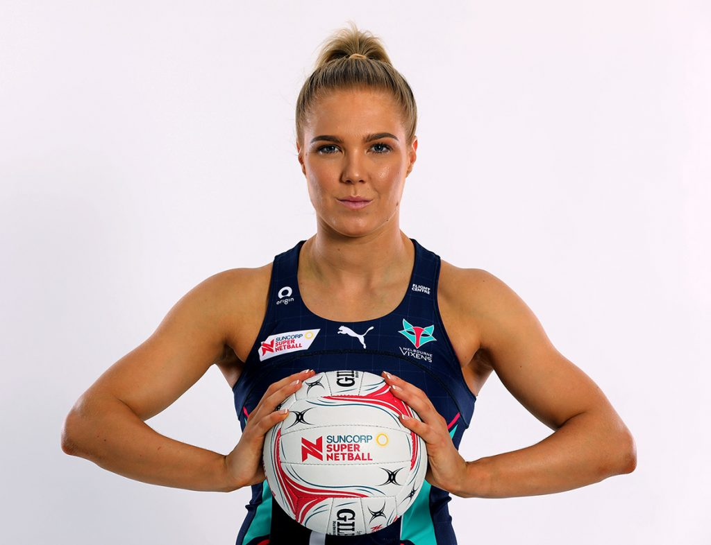 Image is a portrait of Melbourne Vixens captain, Kate Moloney. She stands facing the camera, holding a netball.