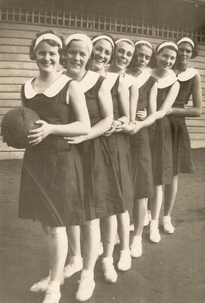 Image is a black and white photo of the Kensington Methodist Ladies basketball (netball) team. The seven women stand in a line, the woman at the front is holding a ball. Siren Sport.