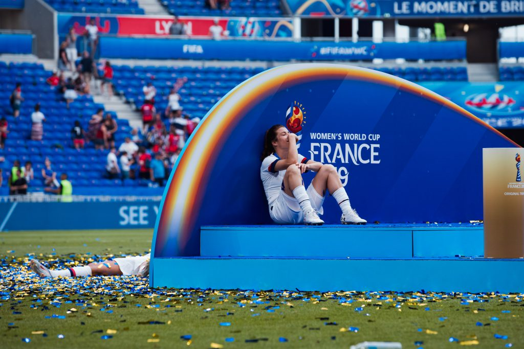 Kelley O'Hara takes a moment after winning the World Cup. USA vs Netherlands, FIFA World Cup Final, 7 July 2019. Image: Rachel Bach