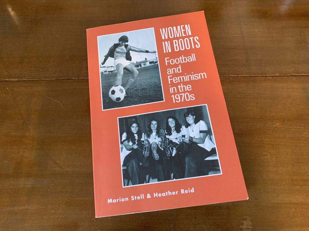 Image is of the book Women in Boots: Football and Feminism in the 1970s. The book is orange and has two photos on the front cover. One in the top left hand corner is off a young woman kicking a soccer ball. The other in the bottom right is a picture of four women, they wear football boots and have pulled up the boots to show the bottoms to the camera.