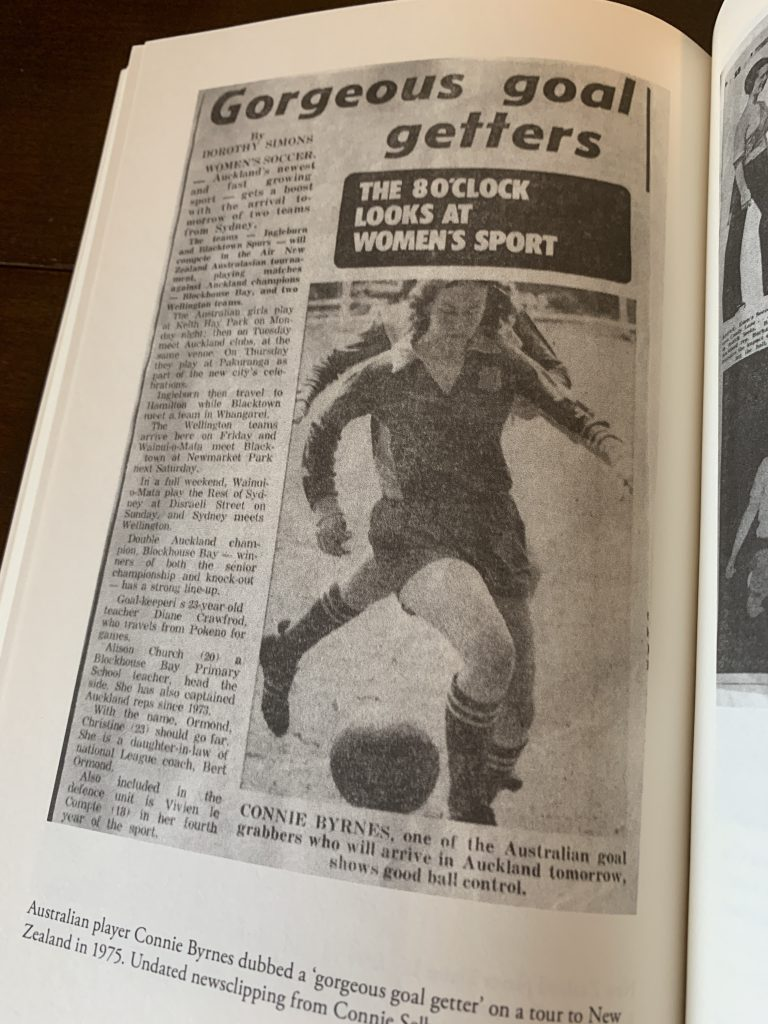 Image is of a page from within the book Women in Boots: Football and Feminism in the 1970s. It shows a newspaper clipping with the headline 'gorgeous goal getters'. A photo underneath the headline shows a woman playing football.