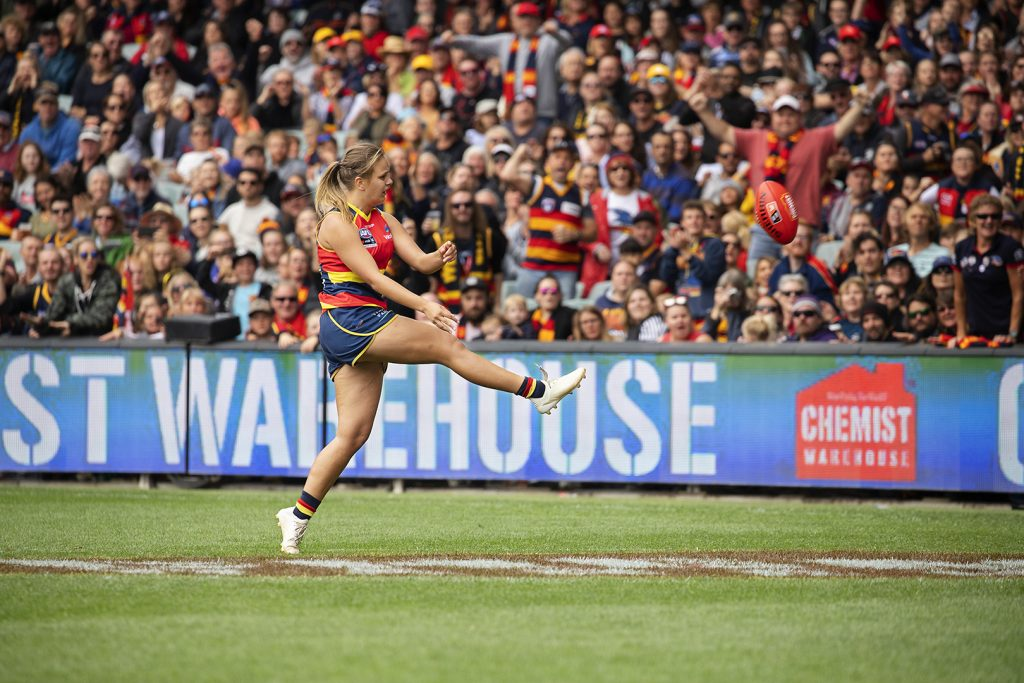 Image is of AFLW footballer, Danielle Ponter. She is in the process of kicking the ball, so her right leg is extended out in front of her. Behind her, you can see a large crowd cheering.