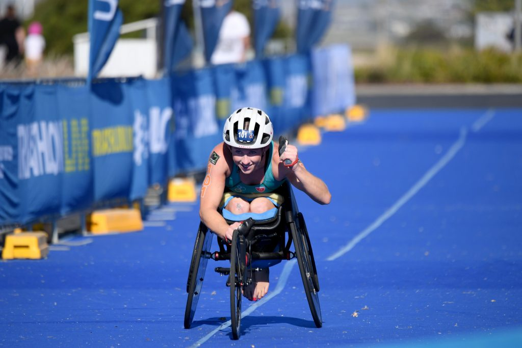 Image is a colour photograph of Lauren Parker coming into the finish line at an event in her racing wheelchair. She wears a white helmet and looks up and ahead of her and is smiling.