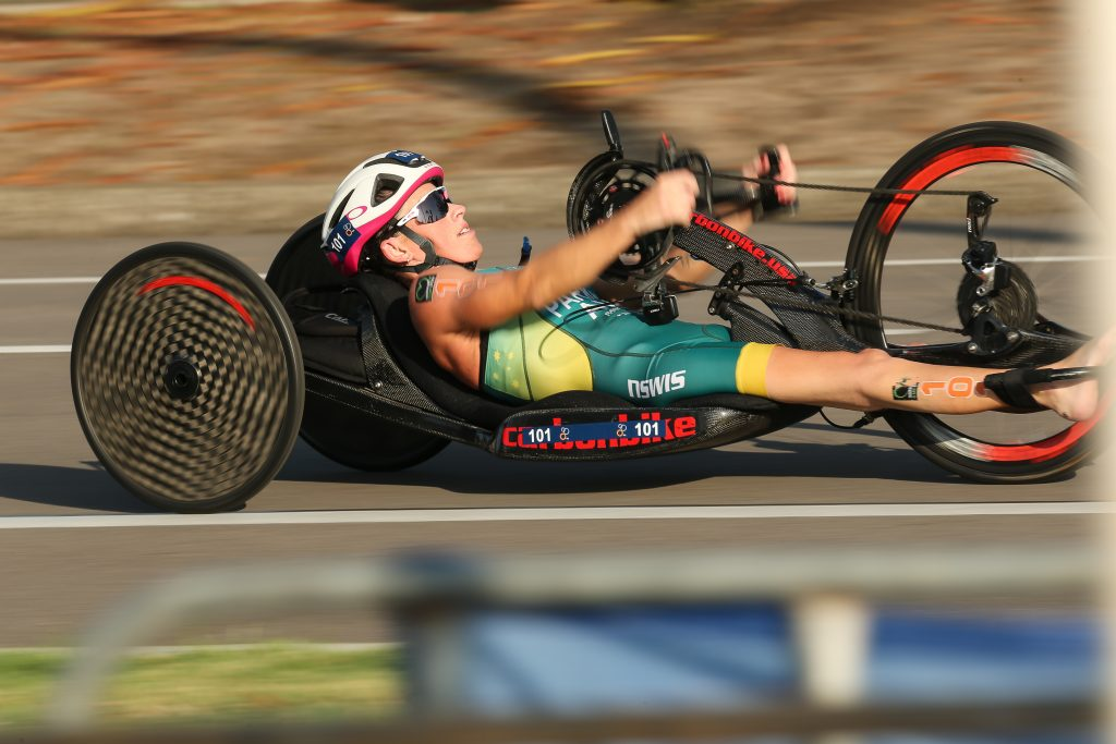 Image is a colour photograph of Lauren Parker racing her hand cycle at an event in Newcastle.