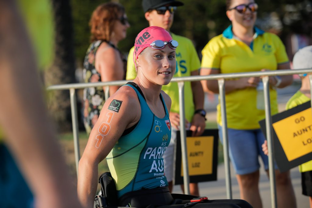 Image is a colour photo of Lauren Parker in her wheelchair. She wears her racing suit, a pink swimming cap and has goggles resting on her forehead. She is looking towards the camera and smiling.