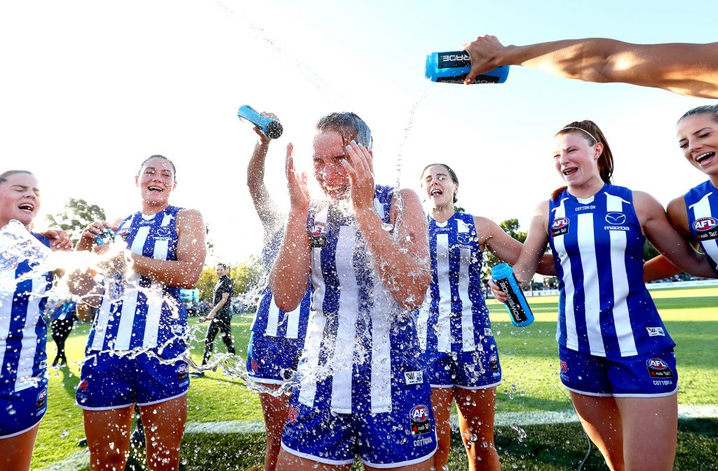 Mia King of the Kangaroos celebrates her debut with teammates after their win against the Gold Coast Suns.