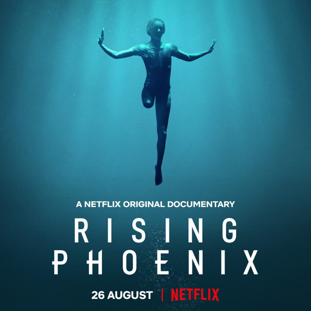 "A caucasian woman is suspended underwater, her right leg ends above the knee, she is wearing a swimsuit and has outstretched arms. White text superimposed on the photo that reads ""A Netflix Original Documentary Rising Phoenix 26 August Netflix"