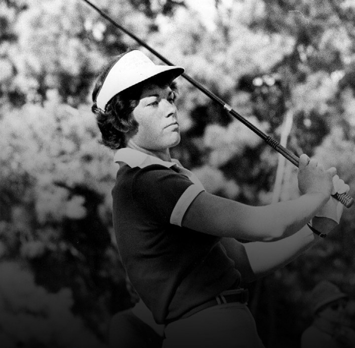 Image is a black and white photograph of Edwina Kennedy. She wears a short sleeved coloured shirt and a visor and swings a golf club.