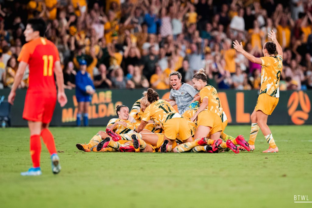 The Matildas celebrate a late goal against China. Image: Rachel Bach / By The White Line