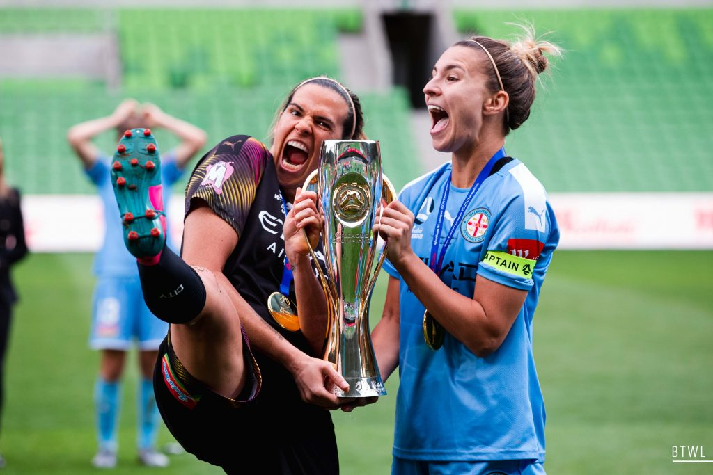 Lydia Williams and Steph Catley celebrate winning the grand final. Image: Rachel Bach / By The White Line