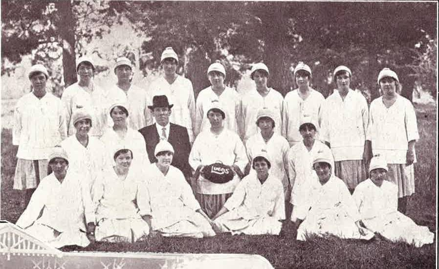 Image is a black and white photo of a team of women footballers. They wear white hats, tunics and skirts.