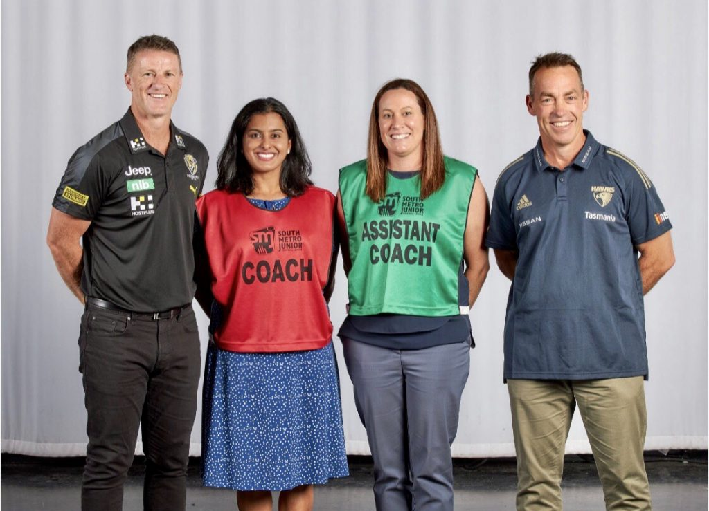 Image is a colour photograph of four people. From left to right, Richmond AFLM coach Damien Hardwick, WCA co-founder Aish Ravi, WCA co-founder Julia Hay, and Hawthorn AFLM coach Alistair Clarkson.