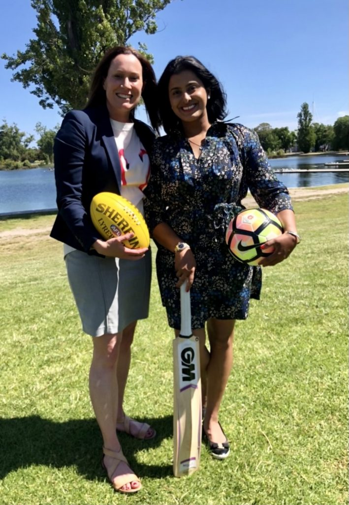 Image is of WCA co-founder Julia Hay and Aish Ravi. They stand close together, smiling at the camera. Julia holds a Sherrin football, while Aish holds a soccer ball and a cricket bat.