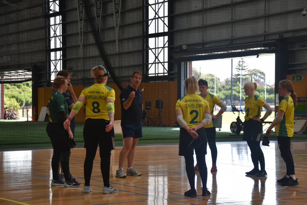 The members of the Aussie Belles stand in in a circle on the court with Coach Peter Corr and Assistant Coach Simon Smith. Peter is speaking to the team.  The players wear they're yellow Australian team shirts and black leggings and shorts.