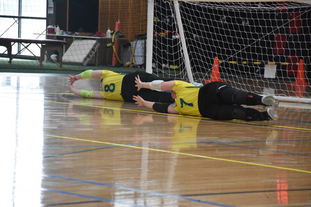Two members of the Aussie Belles demonstrate the way players defend, laying on their sides with their arms and legs outstretched.