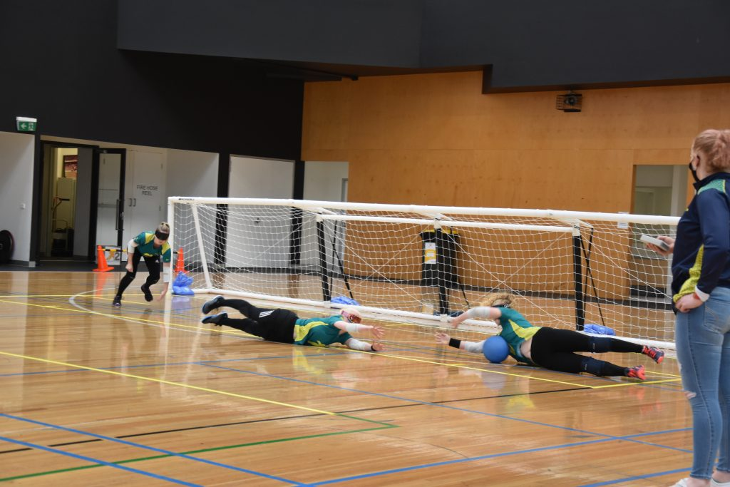 Three members of the Aussie Belles are defening. The two players on the right lay on their sides with their arms and legs stretched out. The ball is hitting the chest of the player on the far right. The player on the far left is crouching, ready to assist if needed.