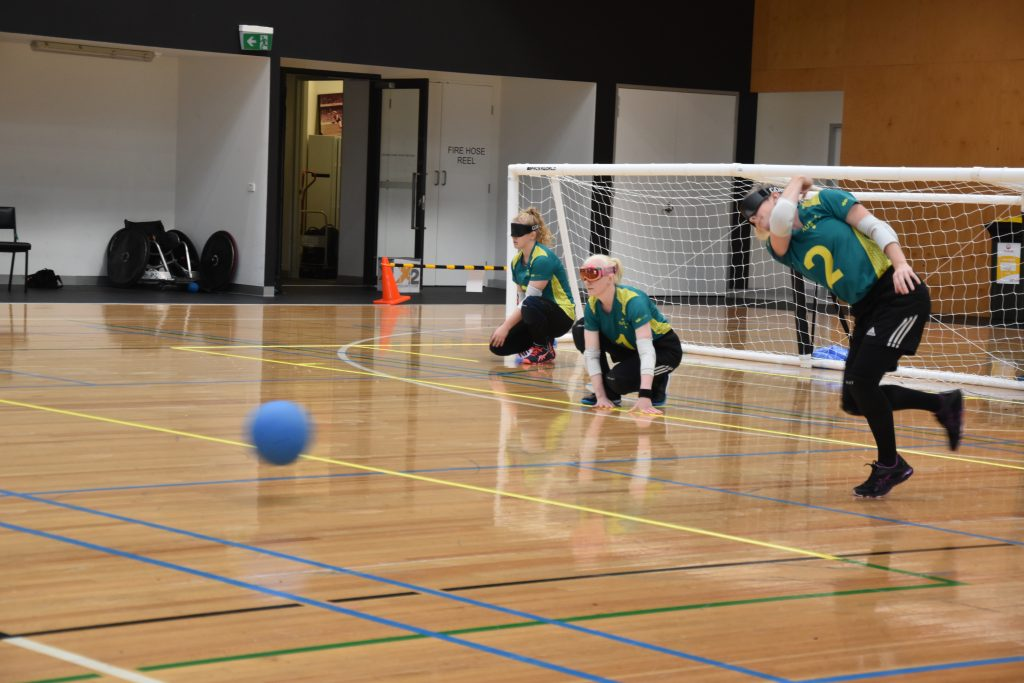 Image is of three of the Aussie Belles set up in offence positions. Two players, the middle and far left, sit crouched while the player on the far right throws the ball towards the opposition.