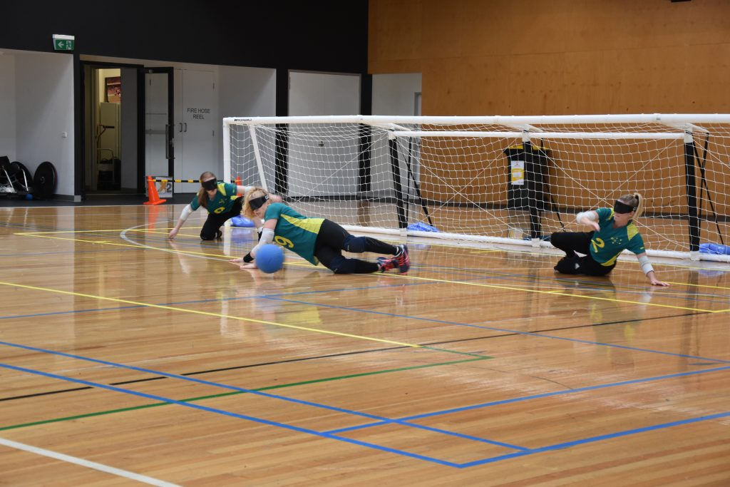Image is of three players from the Aussie Belles defending. They crouch, sit or lay across the court as the blue ball approaches the middle player.