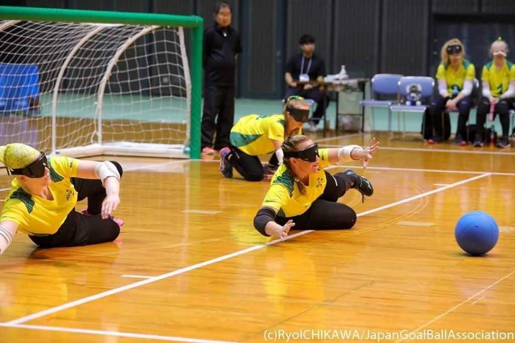 Three of the Aussie Belles are defending, stretching out on their sides with their arms and legs outstretched. The ball is approaching the middle player.