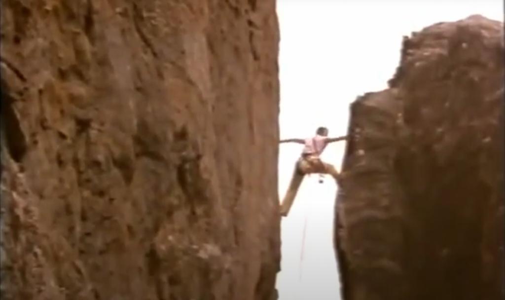 Louise Shepherd climbs in a narrow gap between two boulders.